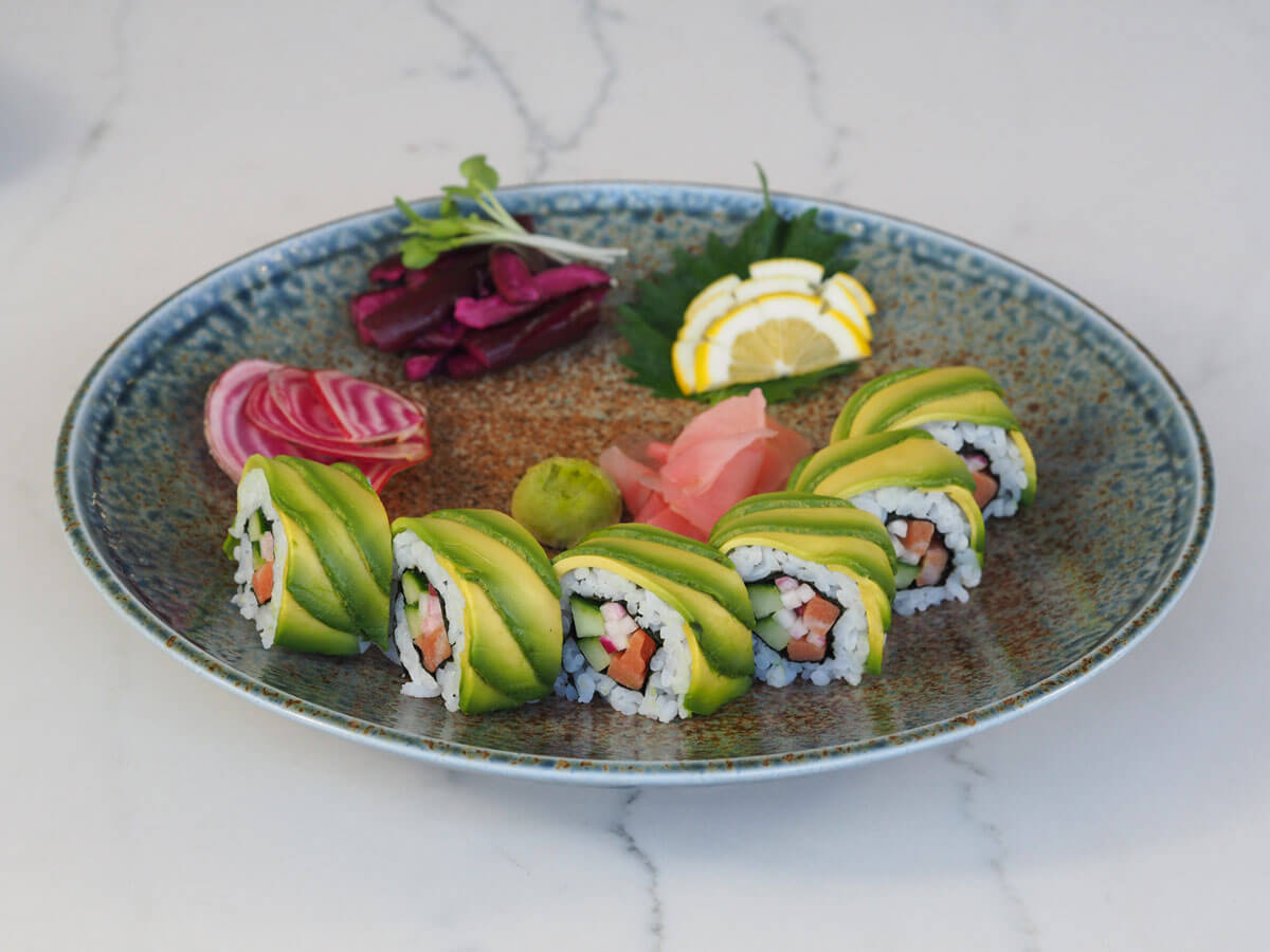 Salmon sushi roll with avocado on the outside