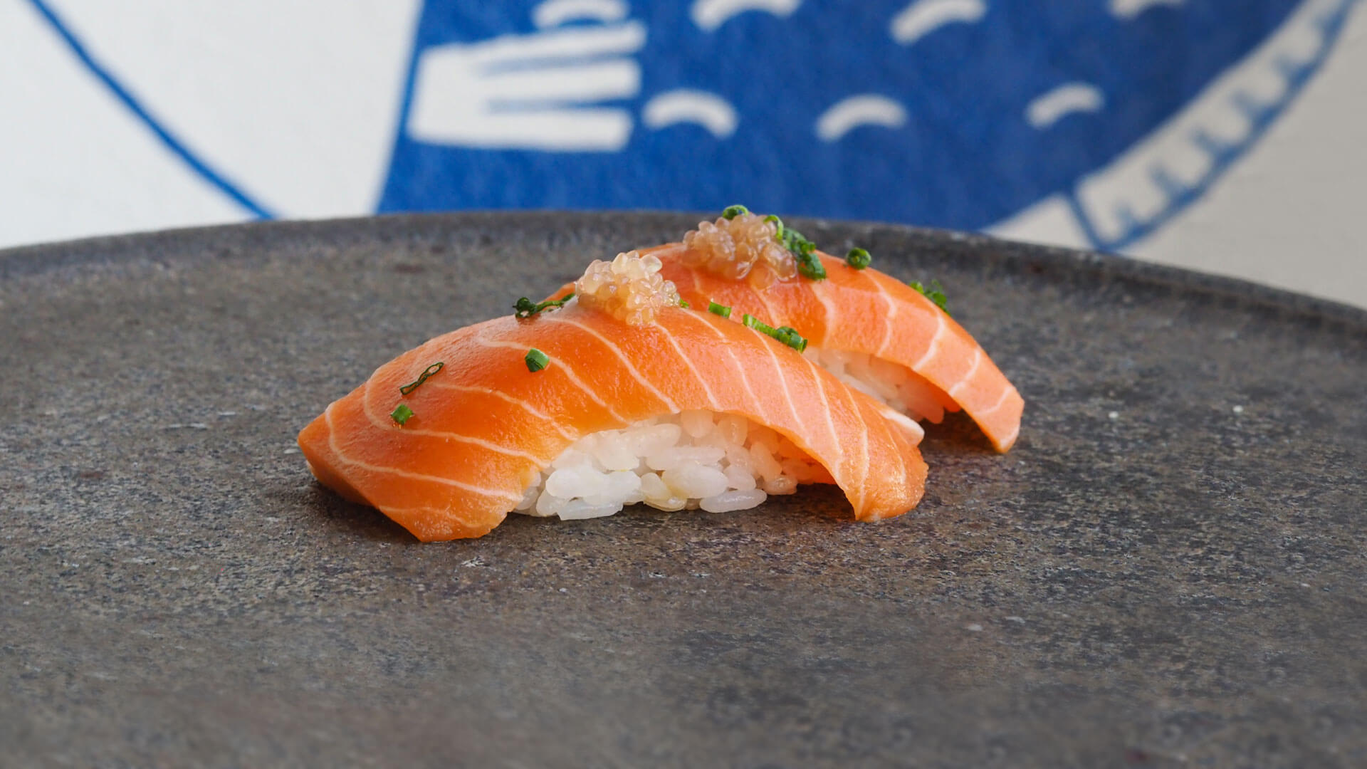 Two pieces of salmon nigiri centered on a large plate