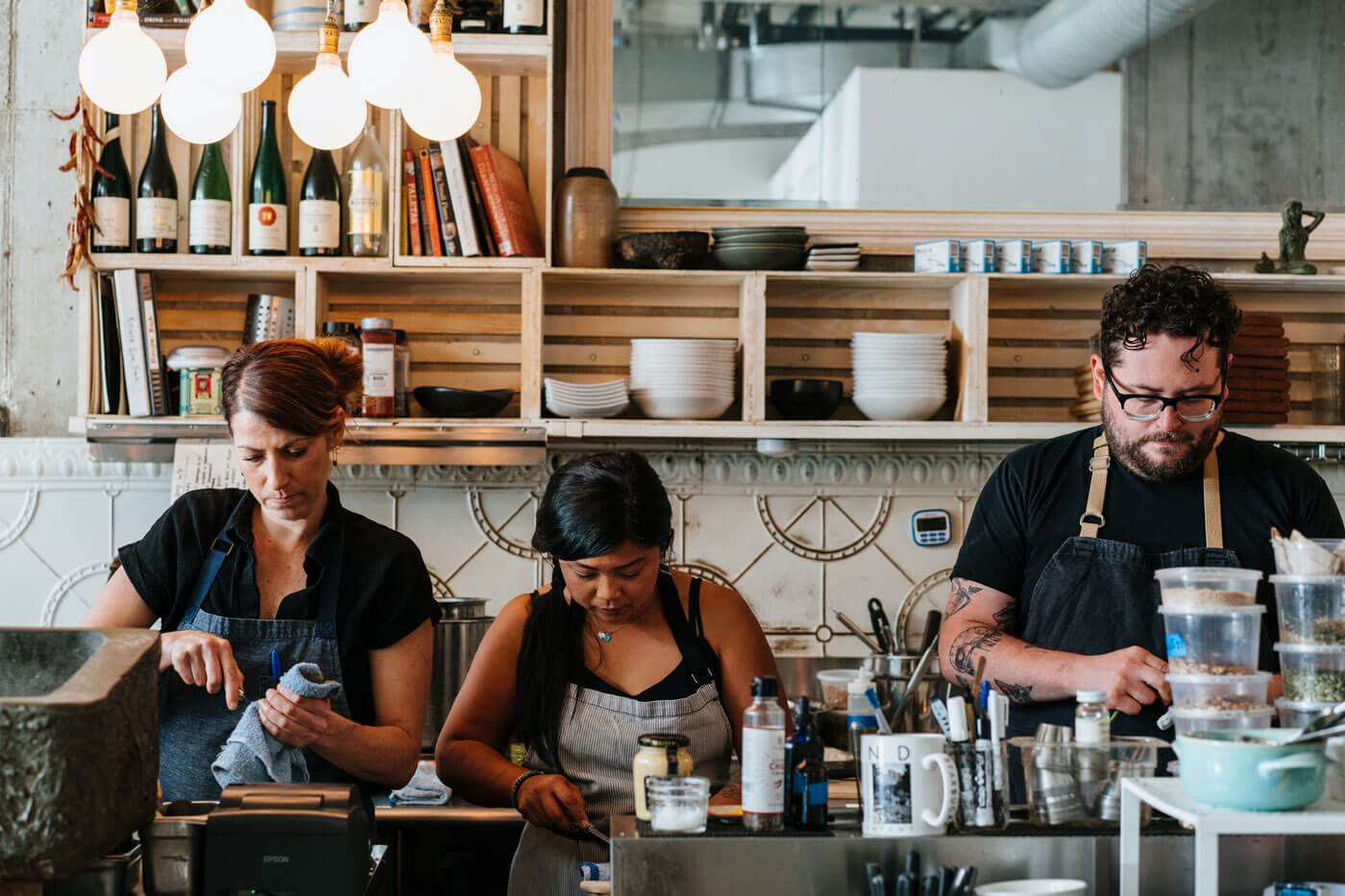 Three employees behind a bar with various spices and dishware